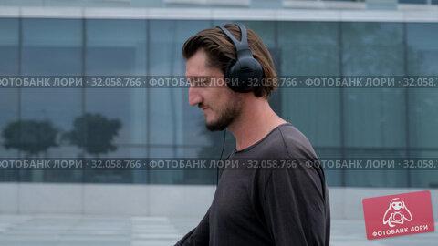 Freelancer Man walking in the big urban city working with a laptop phone camera and listening music via headphones. Стоковое видео, видеограф Aleksejs Bergmanis / Фотобанк Лори