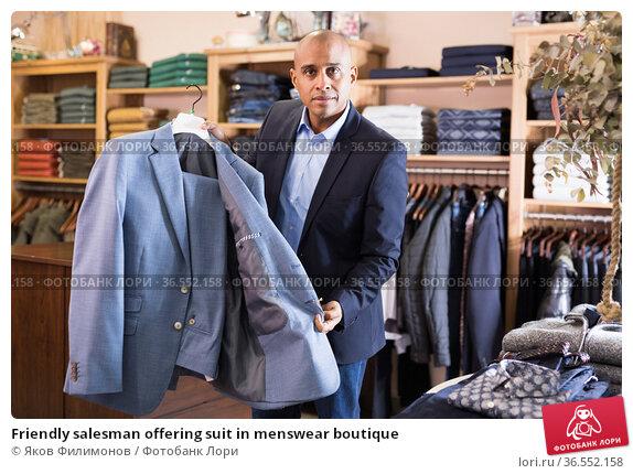 Friendly salesman offering suit in menswear boutique. Стоковое фото, фотограф Яков Филимонов / Фотобанк Лори