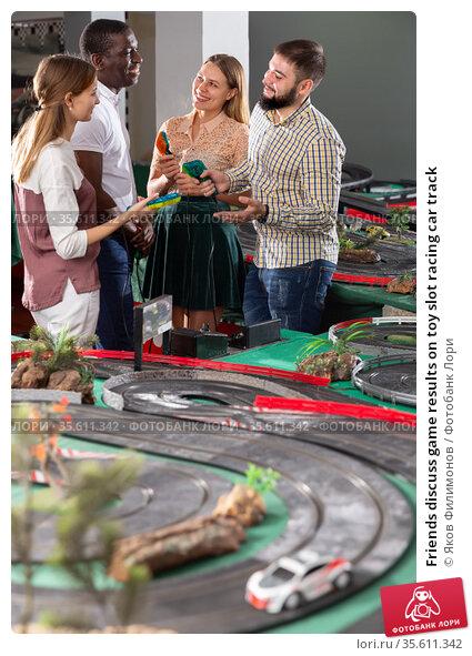 Friends discuss game results on toy slot racing car track. Стоковое фото, фотограф Яков Филимонов / Фотобанк Лори