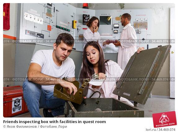 Friends inspecting box with facilities in quest room. Стоковое фото, фотограф Яков Филимонов / Фотобанк Лори