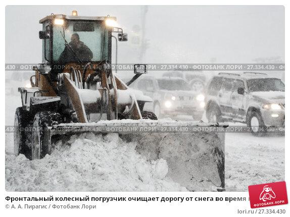 Купить «Фронтальный колесный погрузчик очищает дорогу от снега во время непогоды», фото № 27334430, снято 26 декабря 2017 г. (c) А. А. Пирагис / Фотобанк Лори