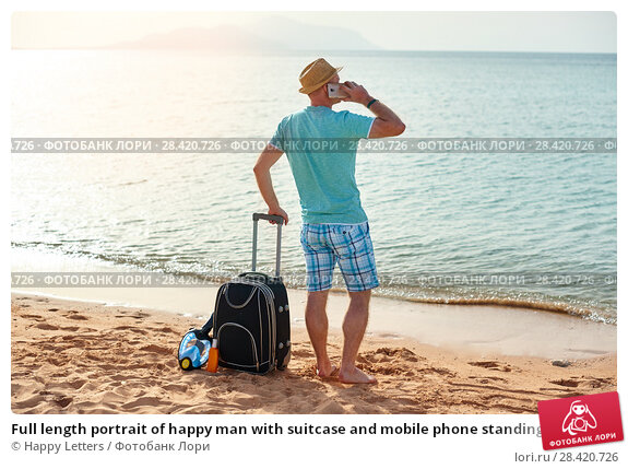 Купить «Full length portrait of happy man with suitcase and mobile phone standing on beach freelancer on a sunny day on vacation», фото № 28420726, снято 19 апреля 2018 г. (c) Happy Letters / Фотобанк Лори