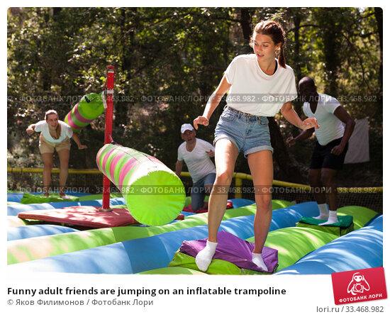 Купить «Funny adult friends are jumping on an inflatable trampoline», фото № 33468982, снято 27 мая 2020 г. (c) Яков Филимонов / Фотобанк Лори