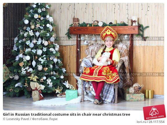 Купить «Girl in Russian traditional costume sits in chair near christmas tree», фото № 28117554, снято 20 ноября 2015 г. (c) Losevsky Pavel / Фотобанк Лори
