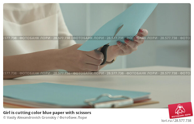 Купить «Girl is cutting color blue paper with scissors», фото № 28577738, снято 20 июня 2018 г. (c) Vasily Alexandrovich Gronskiy / Фотобанк Лори
