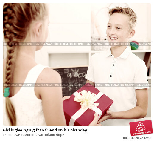Купить «Girl is giveing a gift to friend on his birthday», фото № 26784942, снято 7 августа 2017 г. (c) Яков Филимонов / Фотобанк Лори