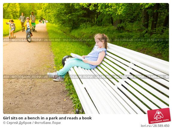 Купить «Girl sits on a bench in a park and reads a book», фото № 28589450, снято 11 июня 2017 г. (c) Сергей Дубров / Фотобанк Лори