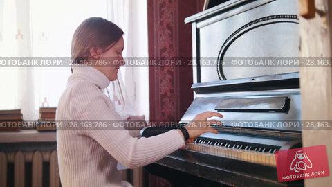 Купить «Girl teen smiles and plays on the piano», видеоролик № 28163786, снято 14 ноября 2018 г. (c) Константин Шишкин / Фотобанк Лори