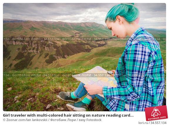 Girl traveler with multi-colored hair sitting on nature reading card... Стоковое фото, фотограф Zoonar.com/Ian Iankovskii / easy Fotostock / Фотобанк Лори