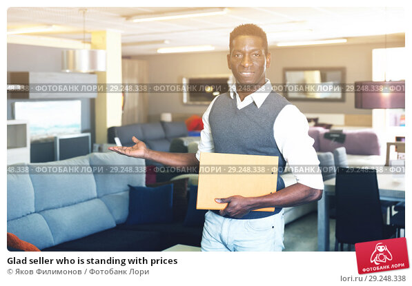 Купить «Glad seller who is standing with prices», фото № 29248338, снято 19 февраля 2018 г. (c) Яков Филимонов / Фотобанк Лори