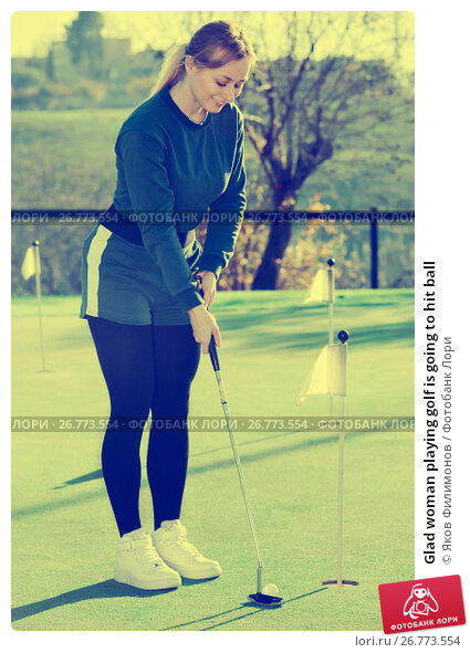 Glad woman playing golf is going to hit ball, фото № 26773554, снято 25 сентября 2017 г. (c) Яков Филимонов / Фотобанк Лори