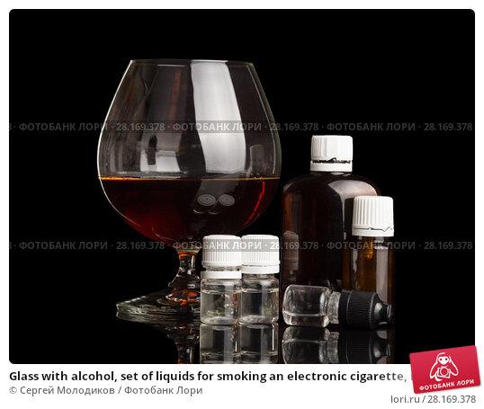 Купить «Glass with alcohol, set of liquids for smoking an electronic cigarette, isolated on black», фото № 28169378, снято 16 июня 2017 г. (c) Сергей Молодиков / Фотобанк Лори