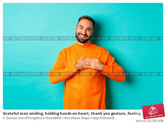 Grateful man smiling, holding hands on heart, thank you gesture, feeling... Стоковое фото, фотограф Zoonar.com/Phongthorn Hiranlikhit / easy Fotostock / Фотобанк Лори