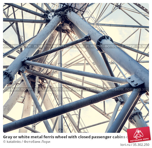 Gray or white metal ferris wheel with closed passenger cabins close-up in the amusement park. Стоковое фото, фотограф katalinks / Фотобанк Лори