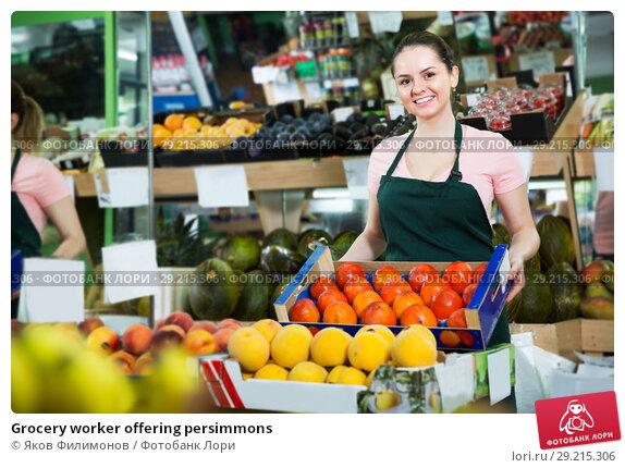 Купить «Grocery worker offering persimmons», фото № 29215306, снято 14 октября 2017 г. (c) Яков Филимонов / Фотобанк Лори