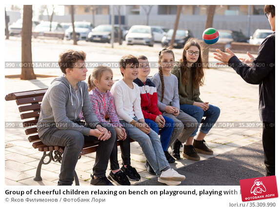 Group of cheerful children relaxing on bench on playground, playing with ball. Стоковое фото, фотограф Яков Филимонов / Фотобанк Лори