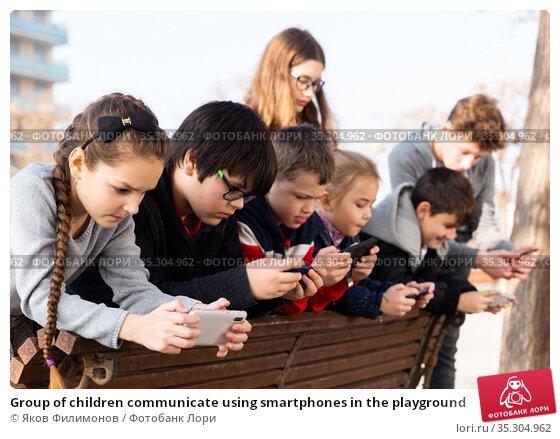 Group of children communicate using smartphones in the playground. Стоковое фото, фотограф Яков Филимонов / Фотобанк Лори
