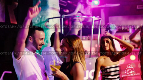 Купить «Group of smiling people clubbing in the night club with drinks», видеоролик № 28151154, снято 7 сентября 2017 г. (c) Яков Филимонов / Фотобанк Лори