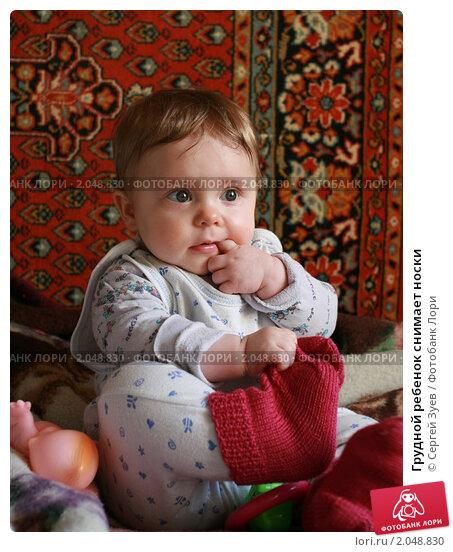 Грудной ребенок снимает носки (2009 год). Редакционное фото, фотограф Сергей Зуев / Фотобанк Лори