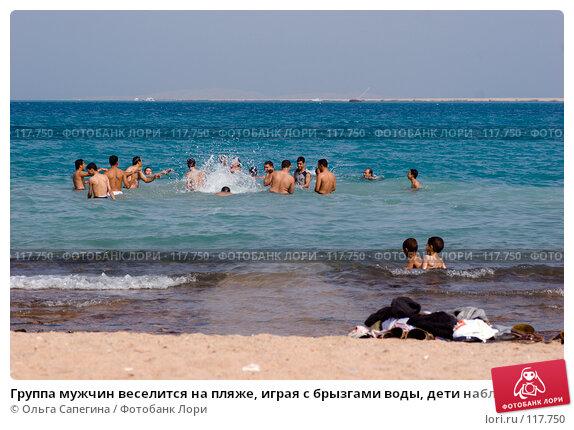 Группа мужчин веселится на пляже, играя с брызгами воды, дети наблюдают, одежда на переднем плане. Африка, Египет, фото № 117750, снято 14 октября 2007 г. (c) Ольга Сапегина / Фотобанк Лори