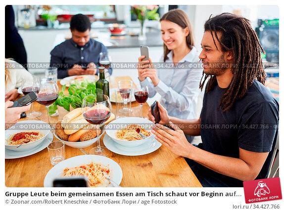 Gruppe Leute beim gemeinsamen Essen am Tisch schaut vor Beginn auf... Стоковое фото, фотограф Zoonar.com/Robert Kneschke / age Fotostock / Фотобанк Лори