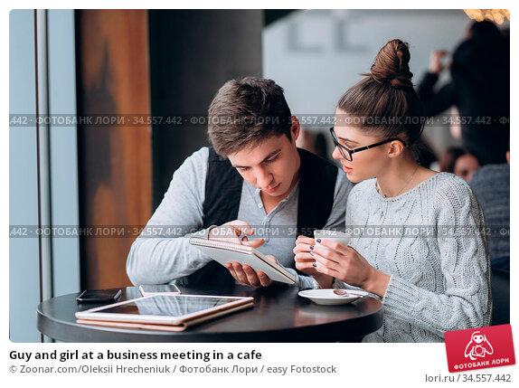 Guy and girl at a business meeting in a cafe. Стоковое фото, фотограф Zoonar.com/Oleksii Hrecheniuk / easy Fotostock / Фотобанк Лори