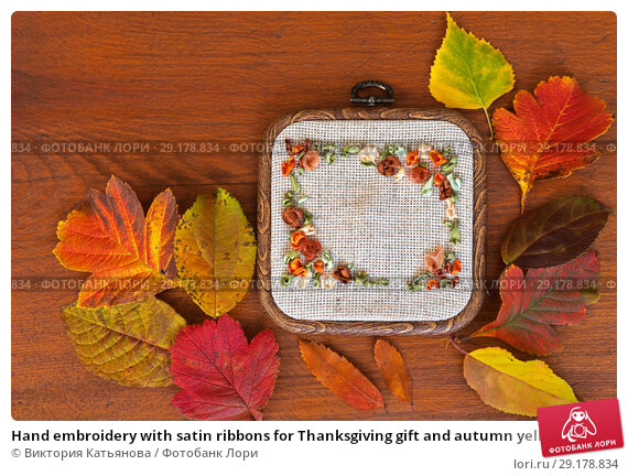 Купить «Hand embroidery with satin ribbons for Thanksgiving gift and autumn yellow and red leaves on an old wooden table», фото № 29178834, снято 2 октября 2018 г. (c) Виктория Катьянова / Фотобанк Лори