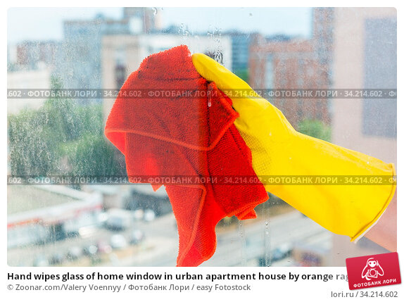 Hand wipes glass of home window in urban apartment house by orange rag. Стоковое фото, фотограф Zoonar.com/Valery Voennyy / easy Fotostock / Фотобанк Лори