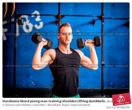 Handsome blond young man training shoulders lifting dumbbells, standing... Стоковое фото, фотограф Zoonar.com/Stefano Cavoretto / easy Fotostock / Фотобанк Лори