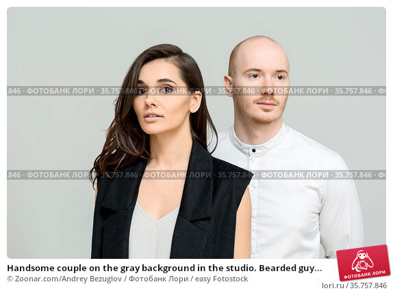 Handsome couple on the gray background in the studio. Bearded guy... Стоковое фото, фотограф Zoonar.com/Andrey Bezuglov / easy Fotostock / Фотобанк Лори