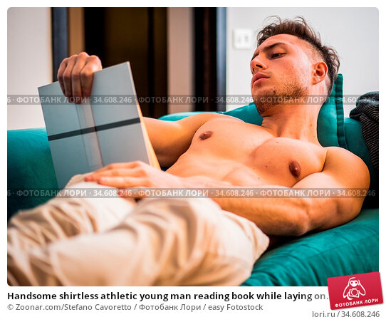 Handsome shirtless athletic young man reading book while laying on... Стоковое фото, фотограф Zoonar.com/Stefano Cavoretto / easy Fotostock / Фотобанк Лори