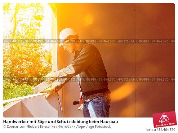 Handwerker mit Säge und Schutzkleidung beim Hausbau. Стоковое фото, фотограф Zoonar.com/Robert Kneschke / age Fotostock / Фотобанк Лори