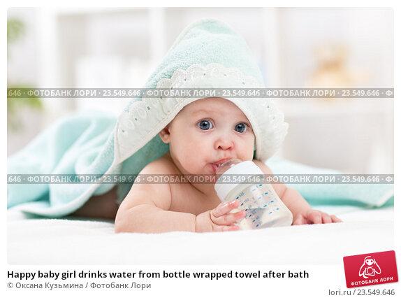 Купить «Happy baby girl drinks water from bottle wrapped towel after bath», фото № 23549646, снято 7 октября 2015 г. (c) Оксана Кузьмина / Фотобанк Лори