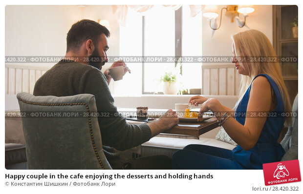 Купить «Happy couple in the cafe enjoying the desserts and holding hands», фото № 28420322, снято 27 мая 2018 г. (c) Константин Шишкин / Фотобанк Лори
