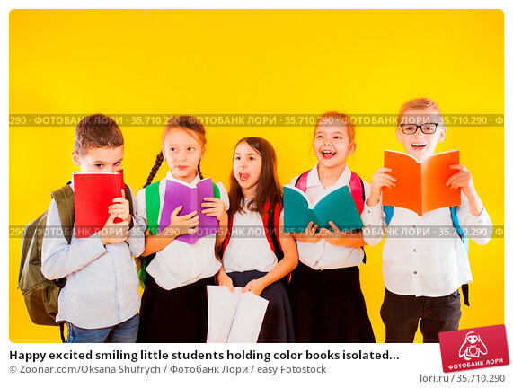 Happy excited smiling little students holding color books isolated... Стоковое фото, фотограф Zoonar.com/Oksana Shufrych / easy Fotostock / Фотобанк Лори