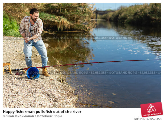 Happy fisherman pulls fish out of the river. Стоковое фото, фотограф Яков Филимонов / Фотобанк Лори