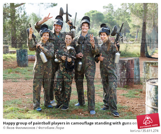 Happy group of paintball players in camouflage standing with guns on paintball playing. Стоковое фото, фотограф Яков Филимонов / Фотобанк Лори