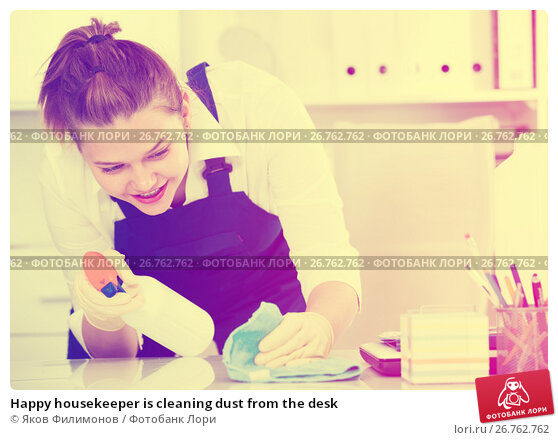 Happy housekeeper is cleaning dust from the desk, фото № 26762762, снято 9 июня 2017 г. (c) Яков Филимонов / Фотобанк Лори