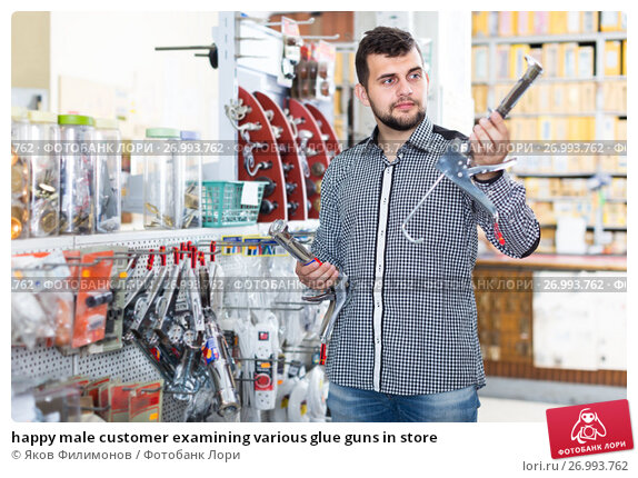 happy male customer examining various glue guns in store. Стоковое фото, фотограф Яков Филимонов / Фотобанк Лори