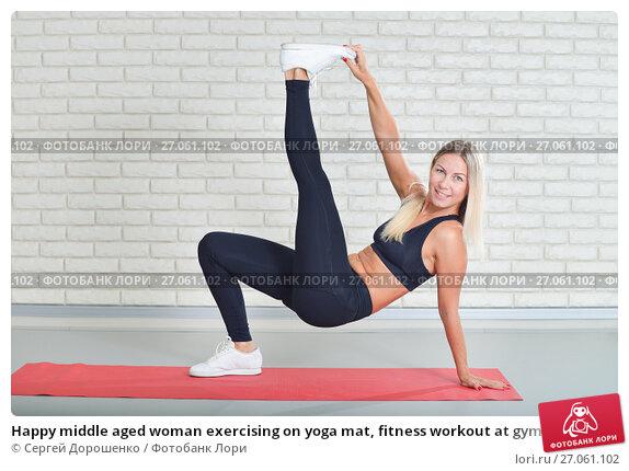 Купить «Happy middle aged woman exercising on yoga mat, fitness workout at gym», фото № 27061102, снято 20 апреля 2018 г. (c) Сергей Дорошенко / Фотобанк Лори
