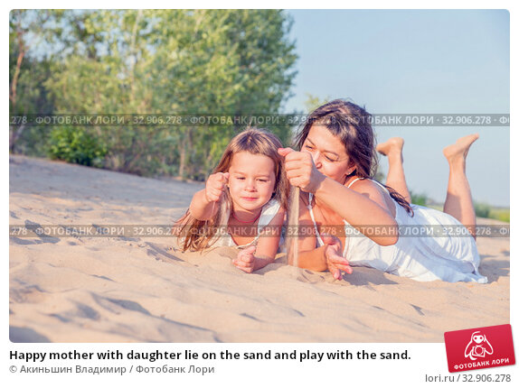 Happy mother with daughter lie on the sand and play with the sand. Стоковое фото, фотограф Акиньшин Владимир / Фотобанк Лори