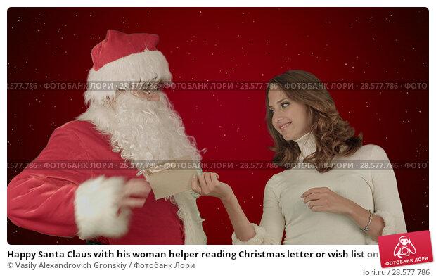 Купить «Happy Santa Claus with his woman helper reading Christmas letter or wish list on red background with snow», фото № 28577786, снято 18 июня 2018 г. (c) Vasily Alexandrovich Gronskiy / Фотобанк Лори