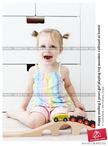 Купить «Happy smiling 2 years girl playing toy wooden railroad at home», фото № 28843722, снято 23 июля 2018 г. (c) ivolodina / Фотобанк Лори