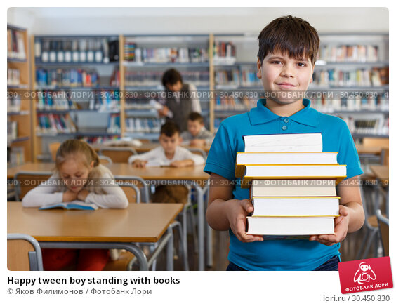 Happy tween boy standing with books. Стоковое фото, фотограф Яков Филимонов / Фотобанк Лори