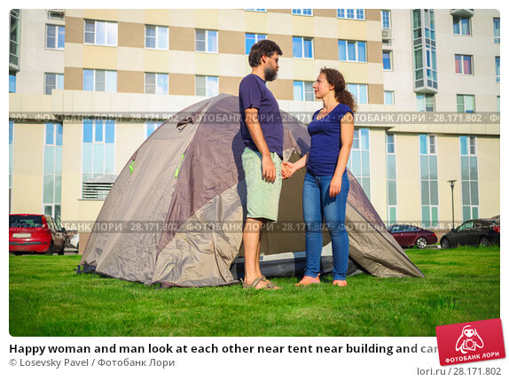 Купить «Happy woman and man look at each other near tent near building and cars at sunny day», фото № 28171802, снято 18 июля 2016 г. (c) Losevsky Pavel / Фотобанк Лори