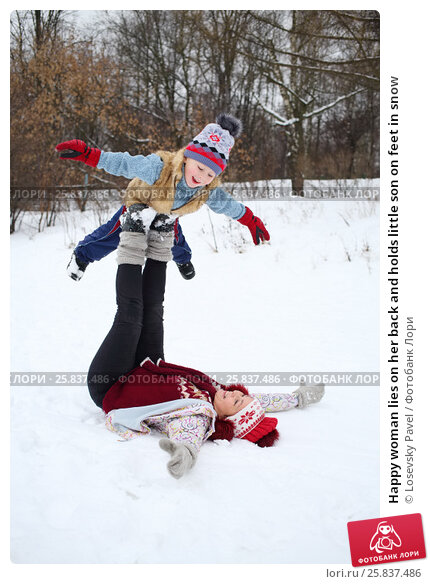 Купить «Happy woman lies on her back and holds little son on feet in snow», фото № 25837486, снято 31 января 2015 г. (c) Losevsky Pavel / Фотобанк Лори