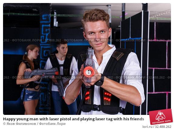 Купить «Happy young man with laser pistol and playing laser tag with his friends», фото № 32488262, снято 27 августа 2018 г. (c) Яков Филимонов / Фотобанк Лори
