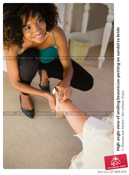 High angle view of smiling beautician putting on sandal to bride, фото № 27069414, снято 2 мая 2017 г. (c) Wavebreak Media / Фотобанк Лори