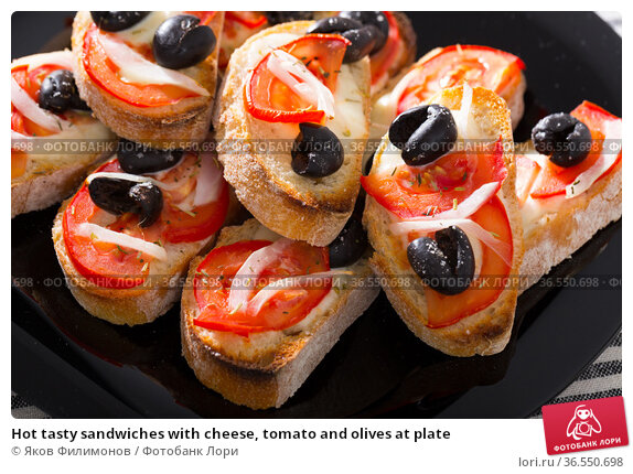 Hot tasty sandwiches with cheese, tomato and olives at plate. Стоковое фото, фотограф Яков Филимонов / Фотобанк Лори