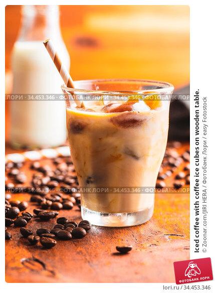 Iced coffee with coffee ice cubes on wooden table. Стоковое фото, фотограф Zoonar.com/JIRI HERA / easy Fotostock / Фотобанк Лори